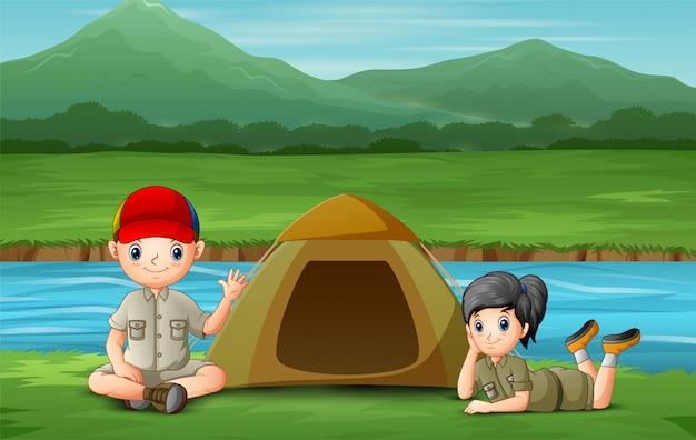 Niños felices acampando en la orilla del río