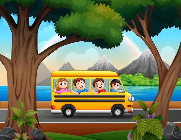 Niños felices en autobús amarillo por la carretera.