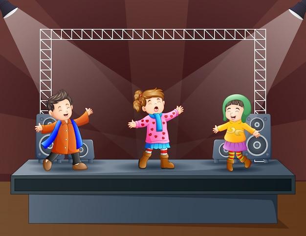 Niños felices cantando en el escenario