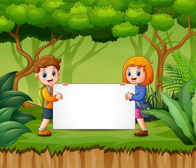 Niños felices con cartel en blanco en el bosque