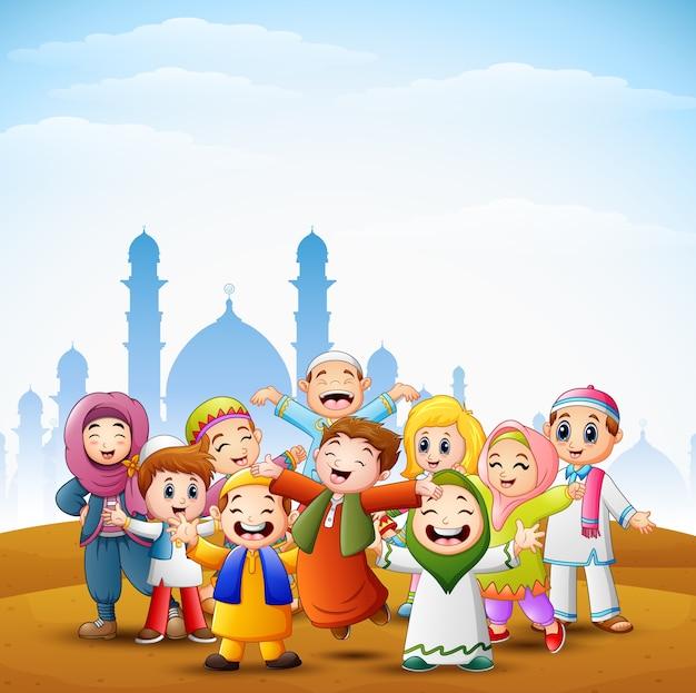 Los niños felices celebran para eid mubarak con el fondo de la mezquita