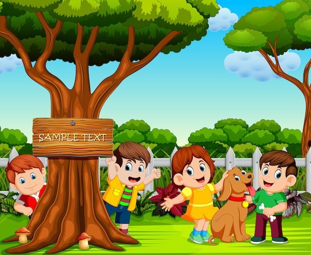 Niños felices están jugando cerca del gran árbol