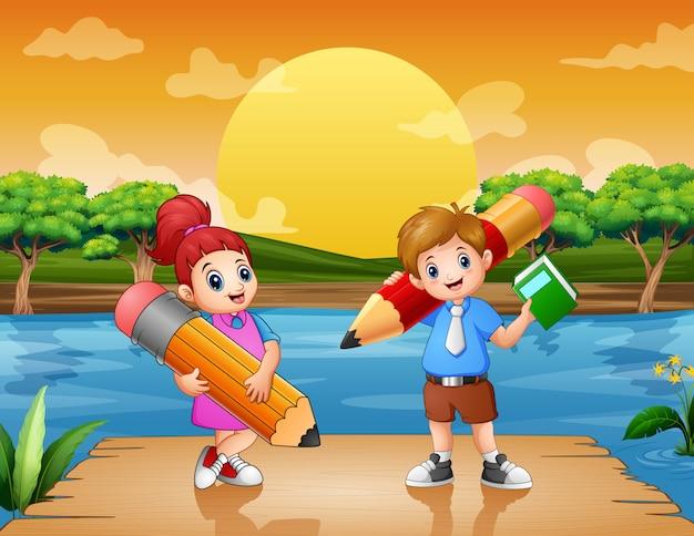 Niños felices con grandes lápices en el muelle