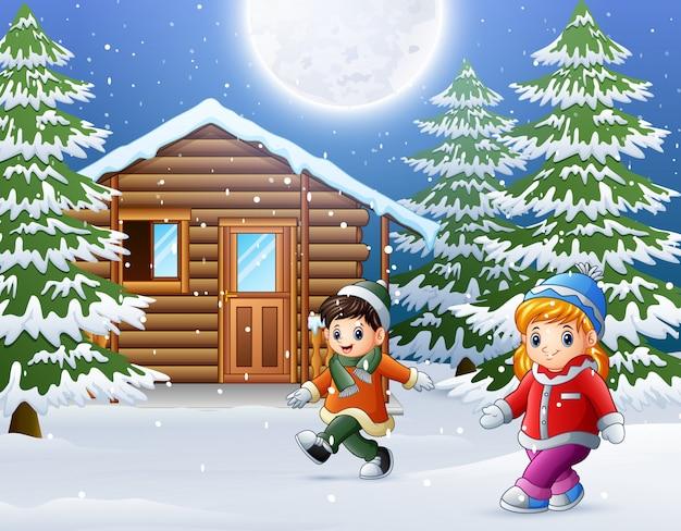 Niños felices juegan frente a una casa de madera nevada