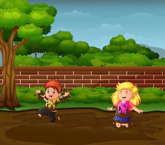 Niños felices jugando en el barro