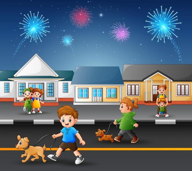 Niños felices jugando en la carretera con vistas de fuegos artificiales en el cielo