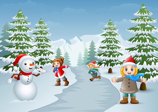 Niños felices jugando con un muñeco de nieve en invierno