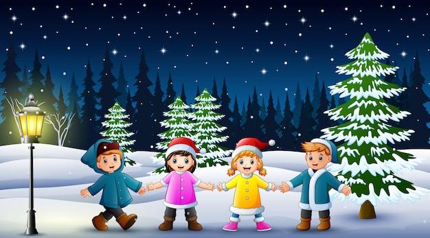 Niños felices jugando en el paisaje de invierno en la noche