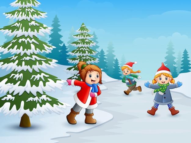 Niños felices jugando en el paisaje de invierno