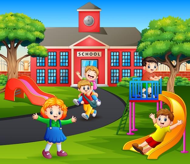 Niños felices jugando en el patio de recreo después de la escuela