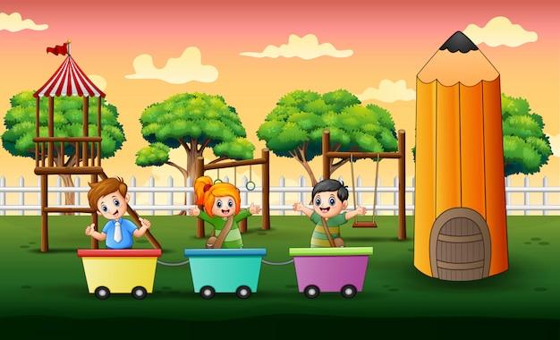 Niños felices jugando en tren en el patio de recreo