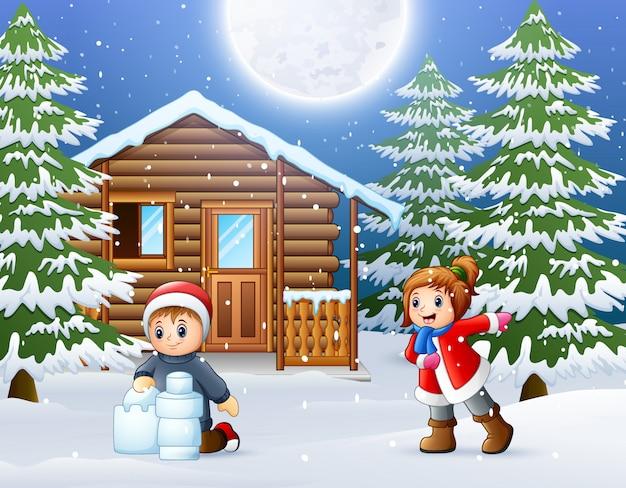 Niños felices y jugar frente a una casa de madera nevada