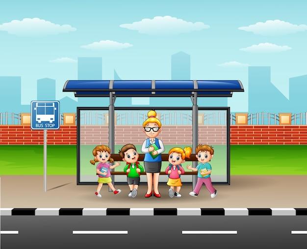 Niños felices, con el maestro en una parada de autobús