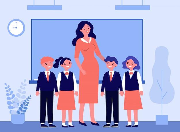 Niños felices y maestro de pie juntos en el aula