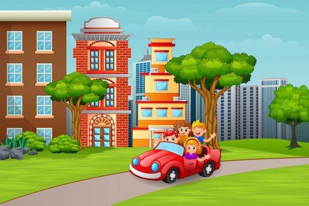 Niños felices montando un auto en el camino a la ciudad