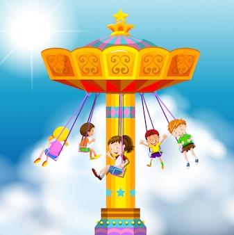 Niños felices montando en columpio gigante
