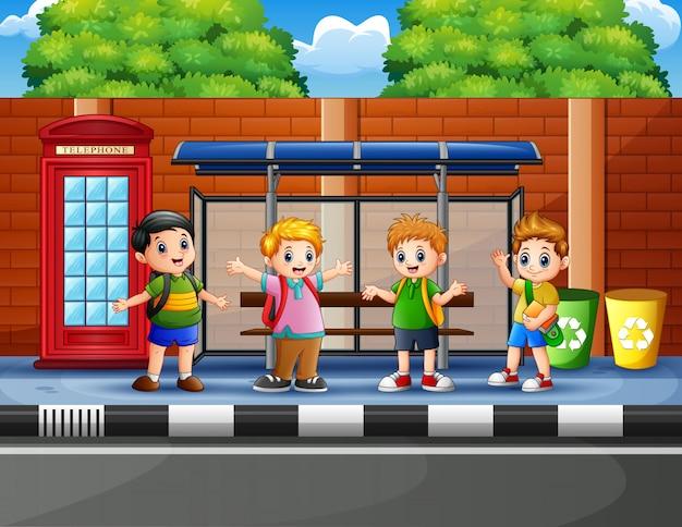 Niños felices en la parada de autobús.