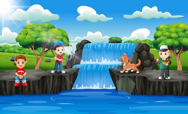 Niños felices pescando en escena de cascada