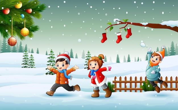 Niños felices que llevan los chlotes de un invierno que juegan en la nieve en el día de navidad