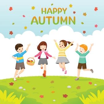 Niños felices saltando juntos en el césped en otoño