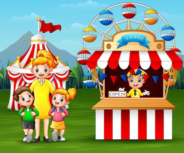 Niños felices y sus padres divirtiéndose en un parque de diversiones