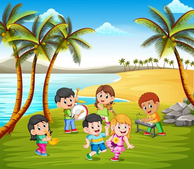Niños felices tocando en banda en la playa