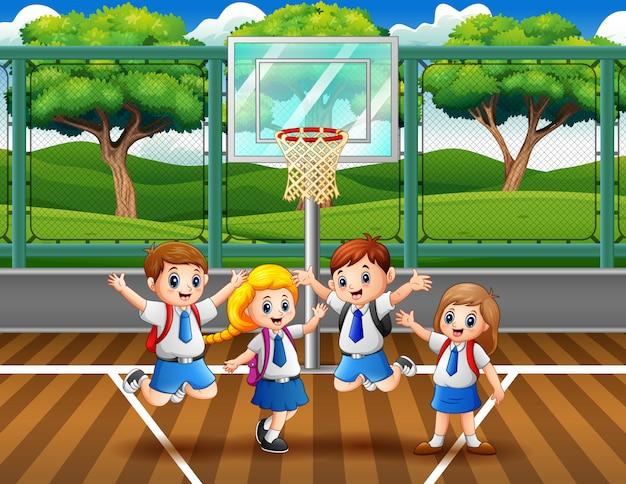 Niños felices en uniforme saltando en la cancha de baloncesto