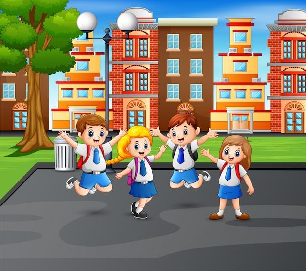 Niños felices en uniforme saltando en el parque