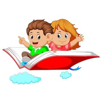 Niños felices volando en gran libro abierto