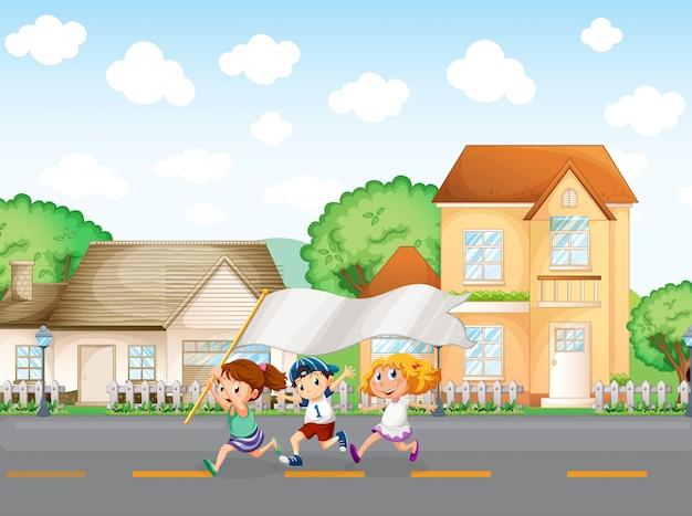 Niños fuera de las casas grandes con una pancarta vacía.