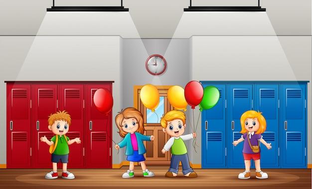 Niños graciosos con globos delante de la clase.