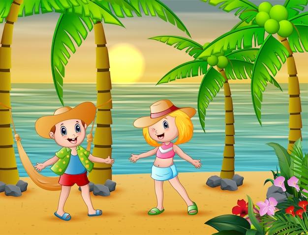 Niños graciosos en la playa con un sombrero de paja