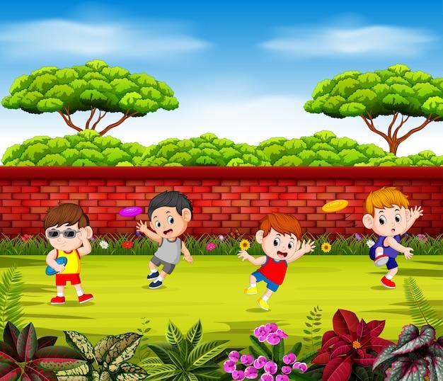 Los niños juegan al frisbee y saltan cerca de la pared roja.