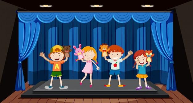 Los niños juegan marionetas de mano en el escenario.
