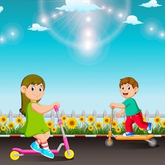 Los niños juegan con el scooter en el jardín.