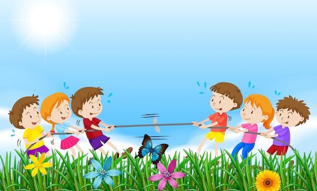 Niños jugando al tirón o la guerra en el campo.