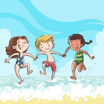 Niños jugando en la orilla de la playa de vacaciones.