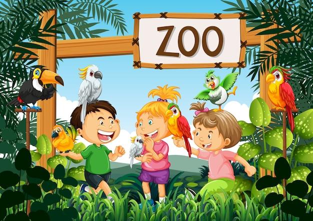Niños jugando con pájaros loro en la escena del zoológico.
