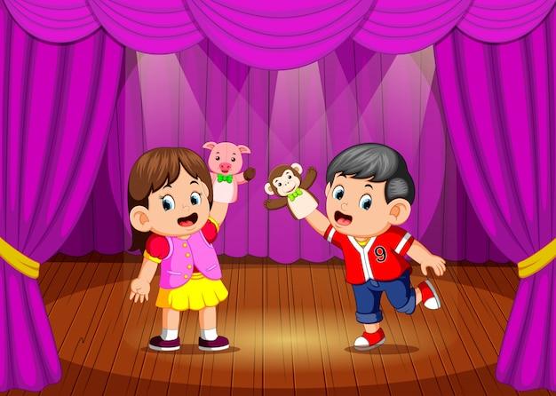 Los niños jugando títeres en el escenario.