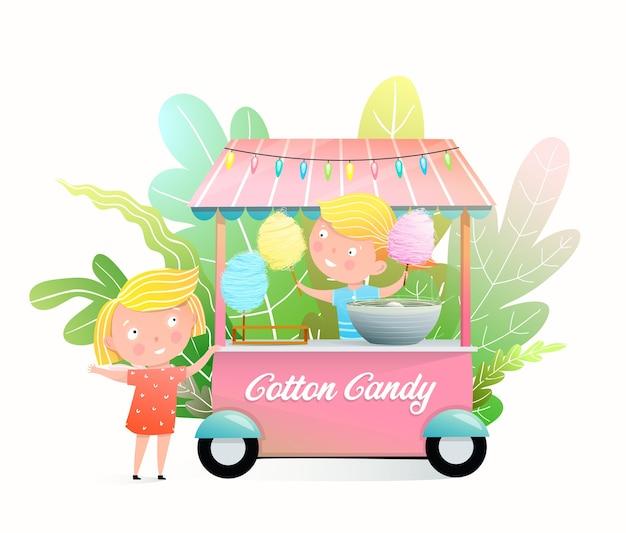 Niños lindos comprando algodón de azúcar en el puesto de feria
