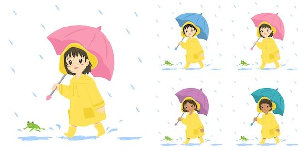 Niños lindos en impermeable amarillo y sosteniendo un paraguas, conjunto.