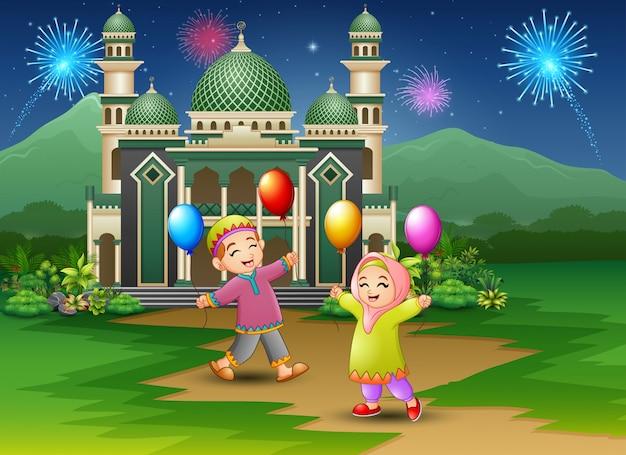 Niños musulmanes felices sosteniendo globos delante de la mezquita