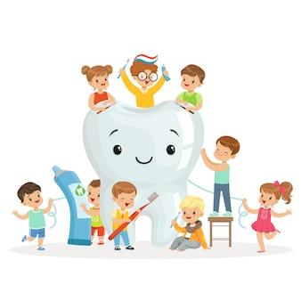 Los niños pequeños cuidan y limpian un diente grande y sonriente. personajes de dibujos animados coloridos