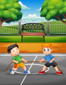 Niños pequeños jugando al tira y afloja en la corte