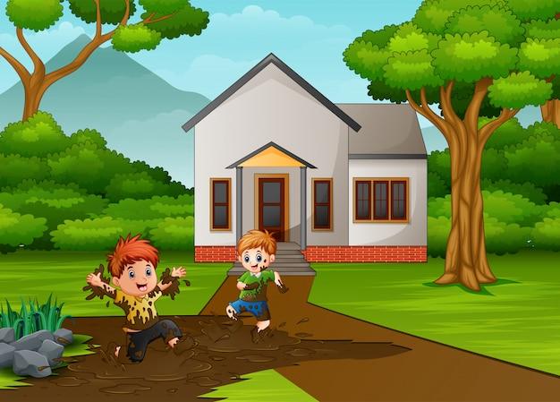 Niños pequeños jugando un barro delante de la casa