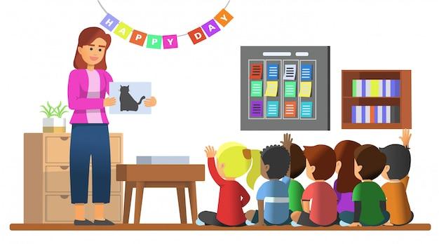 Niños pequeños que estudian junto con su maestra