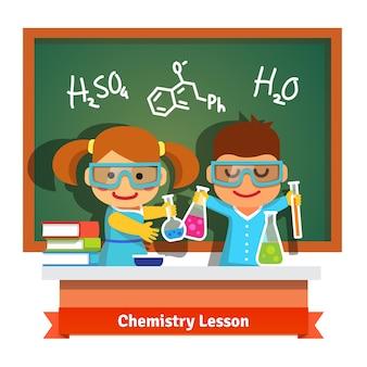 Niños que se divierten en la lección de la química
