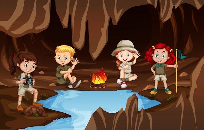 Niños que tienen un campire en una cueva