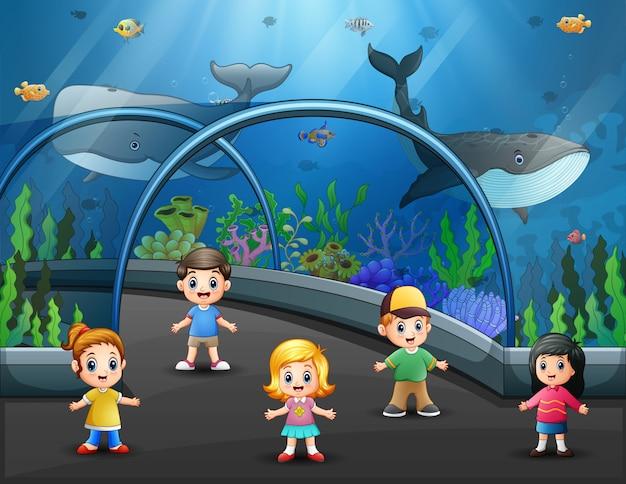 Niños que visitan el acuario lleno de peces ilustración