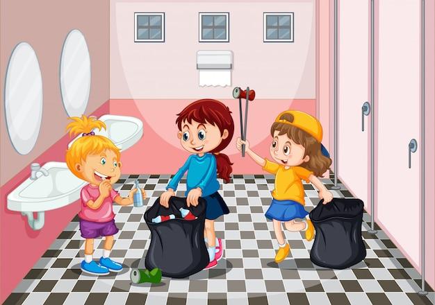 Niños recogiendo basura en el baño.